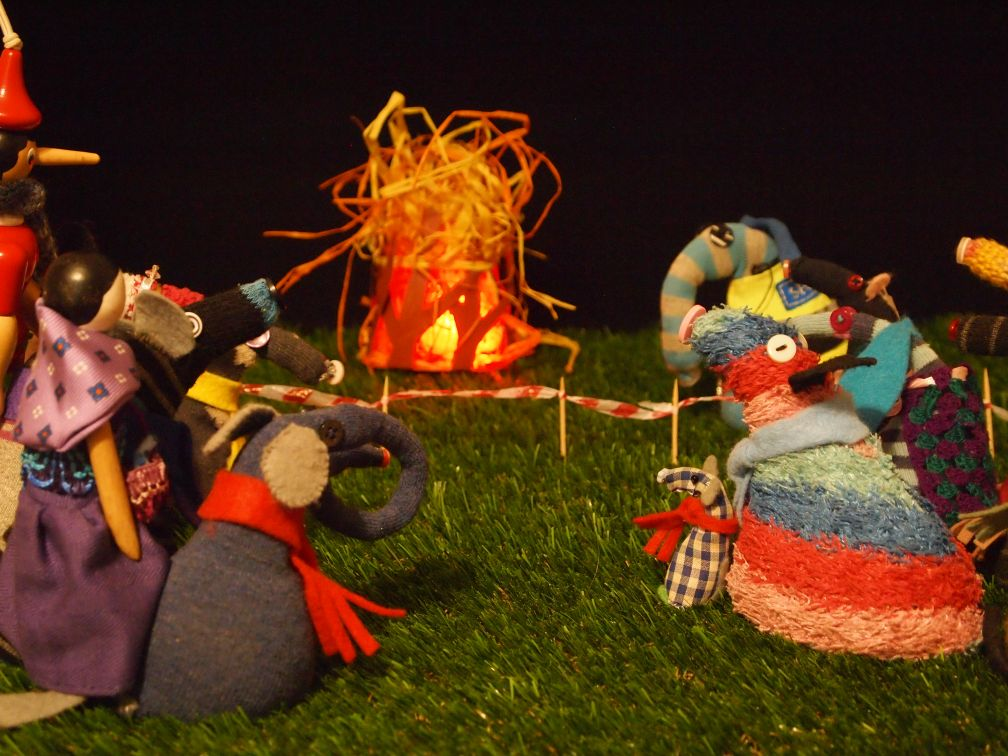 Arnold lights the bonfire which glows red