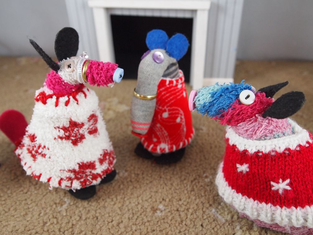 Matilda and Dim show off their sweaters to ratvaark. Matilda's is cream with red snowflakes