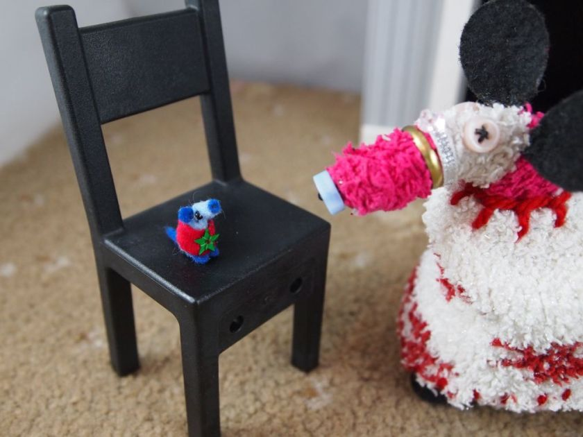 Nano sits on a chair wearing a red sweater with a green star sequin sewn on the front