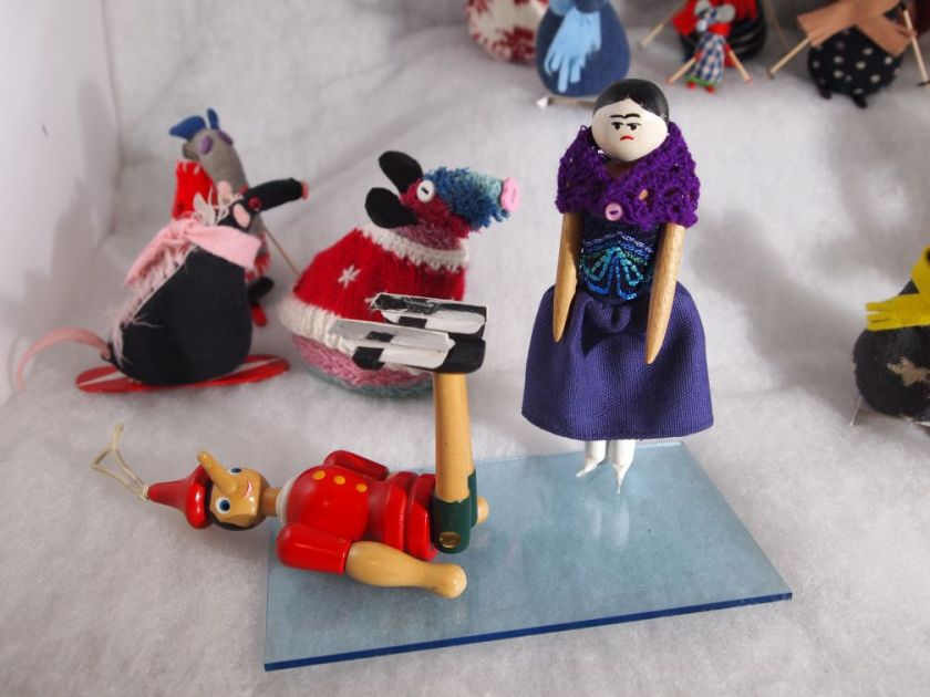 Peggy and Gino are on a shiny ice rink, wearing skates, but Gino has fallen on his back and has his feet in the air