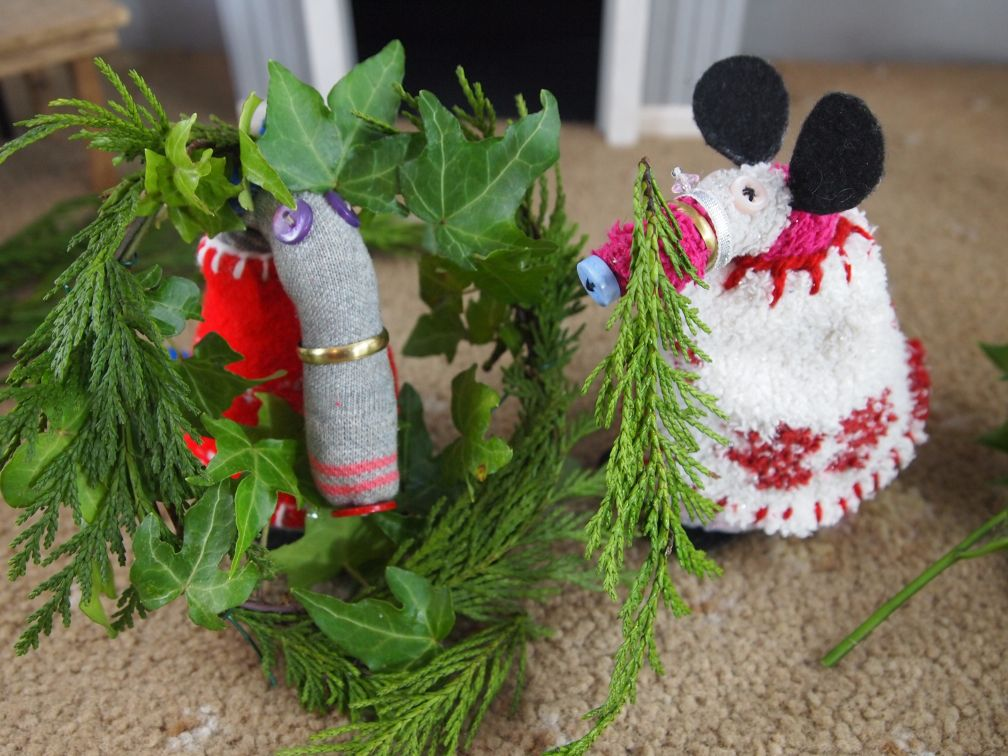 Dim holds the wreath while Matilda weaves in some conifer