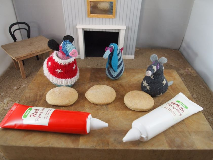 Ratvaark, Ofelia and Vincent sit on a chopping board with three plain biscuits and two tubes of icing, one red, one white