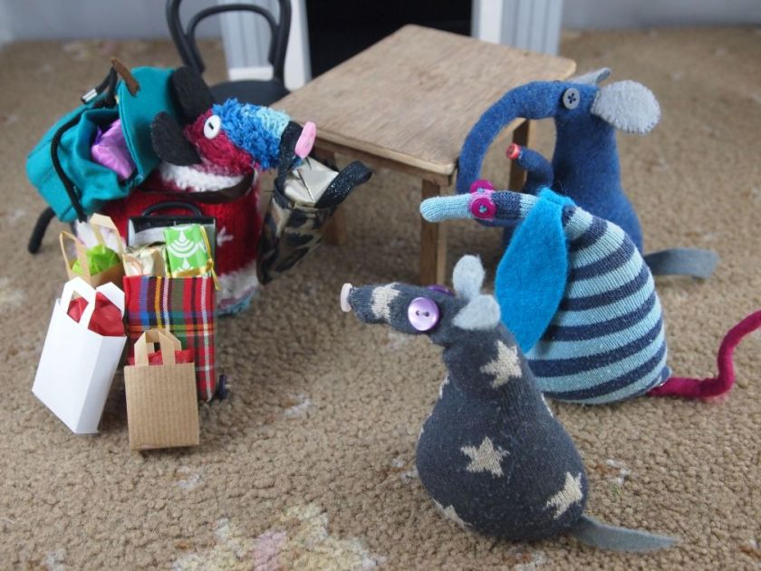 Ratvaark is back in the room, carrying a rucksack, a shopiing bag, with a shopping trolley and a few paper carrier bags, talking to Ernest Ofelia and Vincent