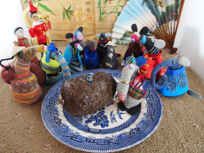 The vaarks gather around a willow pattern plate on which a haggis sits. Dim plays the bagpipes, and Nano sits on the haggis