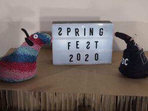 Ratvaark and Fury look at a sign saying Spring Fest 2020, but all the s are the wrong way round