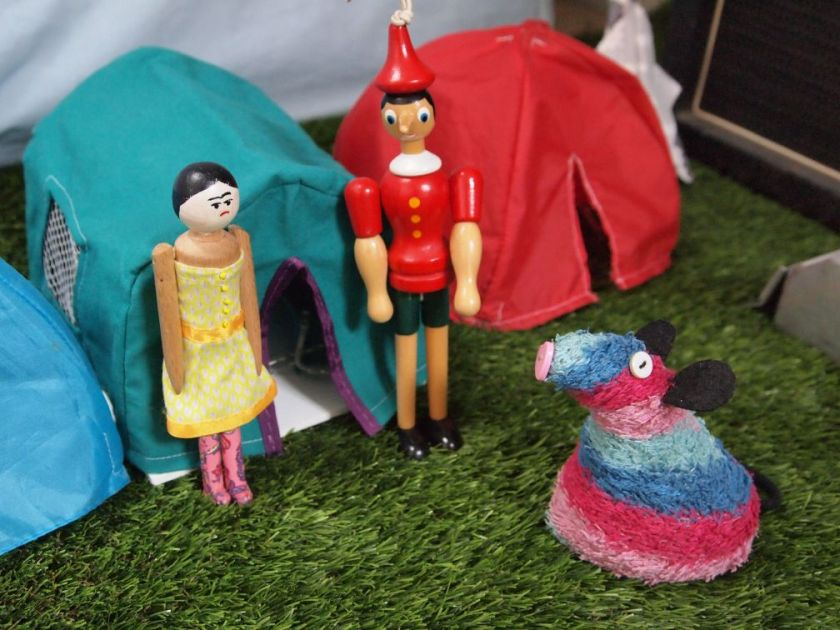 Ratvaark talks to Peggy and Gino outside their tent. Peggy wears a pair of pink floral wellies