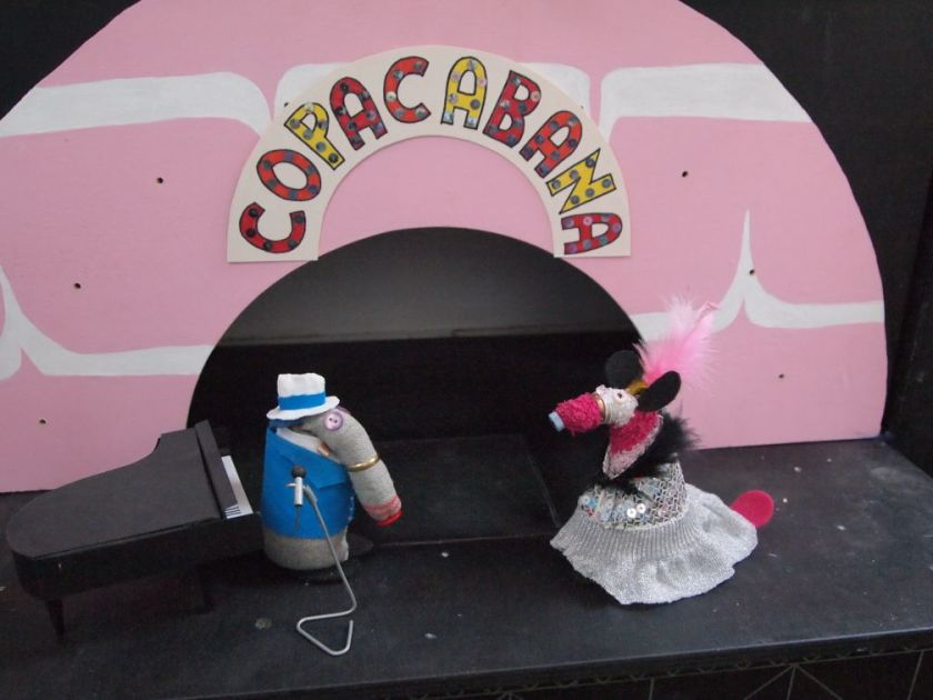 Dim and Matilda dance under a shiny sign that reads Copacabana.
