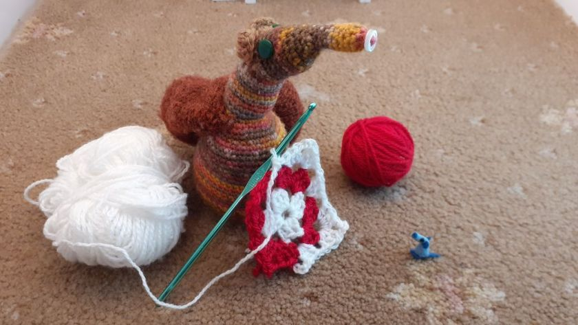 Esther is crocheting a red and white granny square