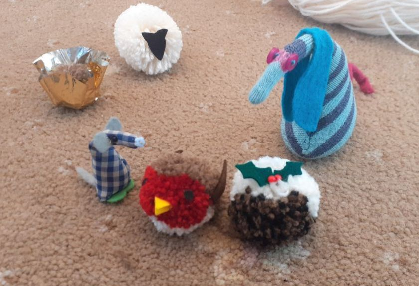 Micro and ofelia look at pompoms made to look like a robin and a christmas pudding