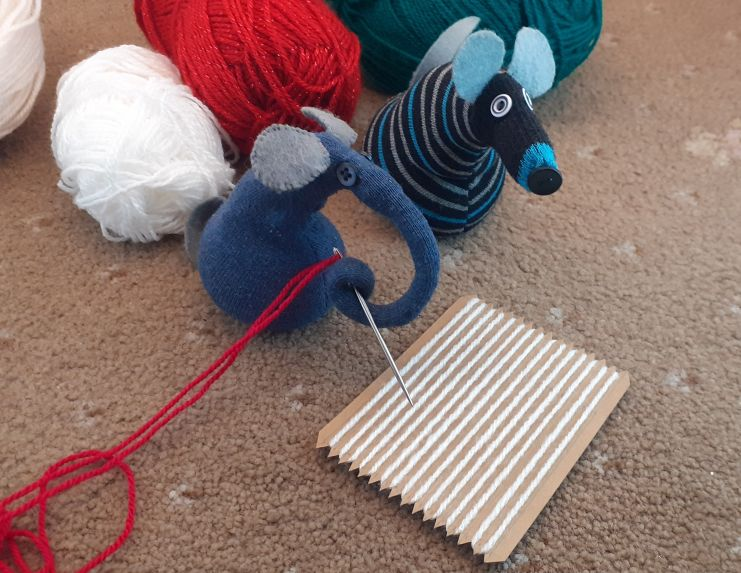 Ernest has a needle threaded with red yarn