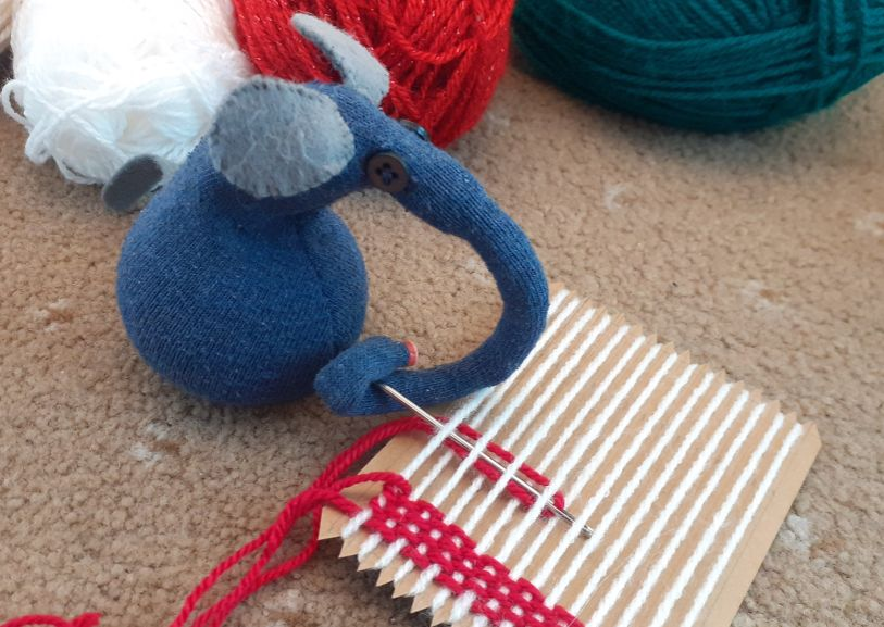 Ernest starts to weave the red yarn in and out