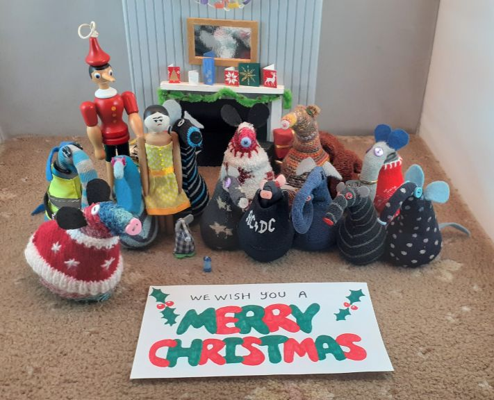 """All the vaarks and Peggy and Gino stand behind the finished banner which reads """"We wish you a Merry Christmas"""""""
