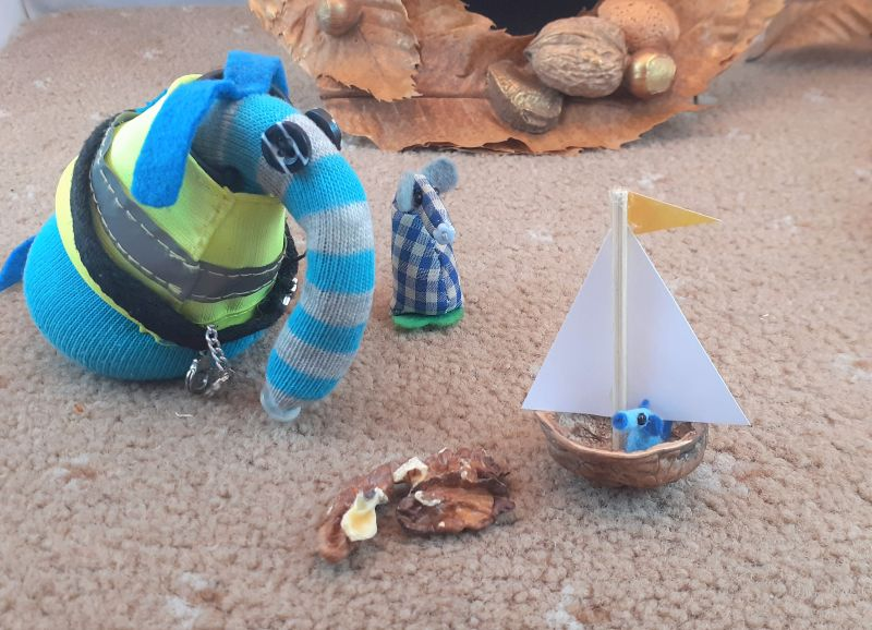 Nano sits in a half walnut shell, with a mast and sail to look like a yacht.