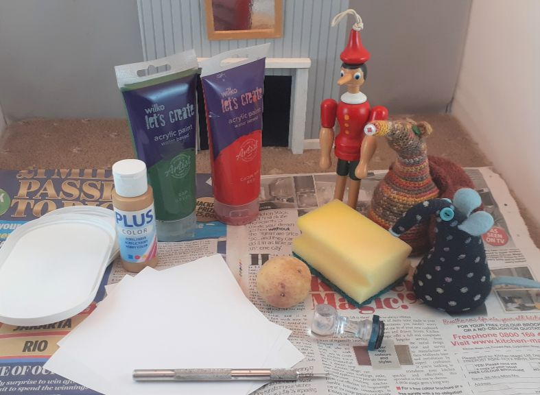 Winston, Esther and Gino have gathered together paper, paint, a sponge, a potato, all on a sheet of newspaper.