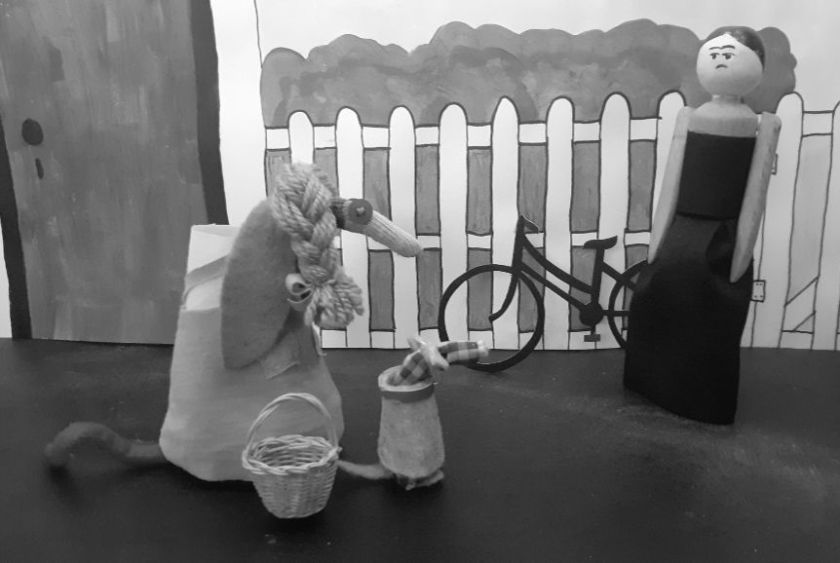 Peggy arrives as Miss Gulch, in a black dress, with a bicycle