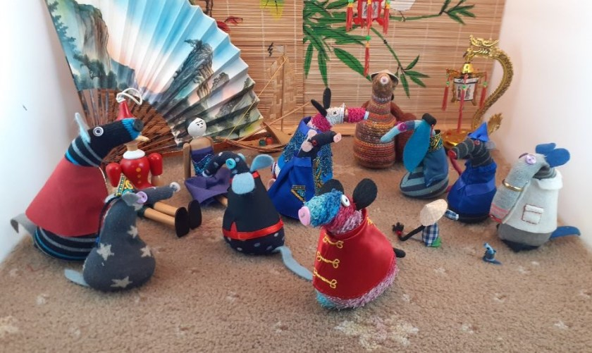 All the vaarks are gathered in front of a painted bamboo backdrop, wearing chinese style jackets or hats.