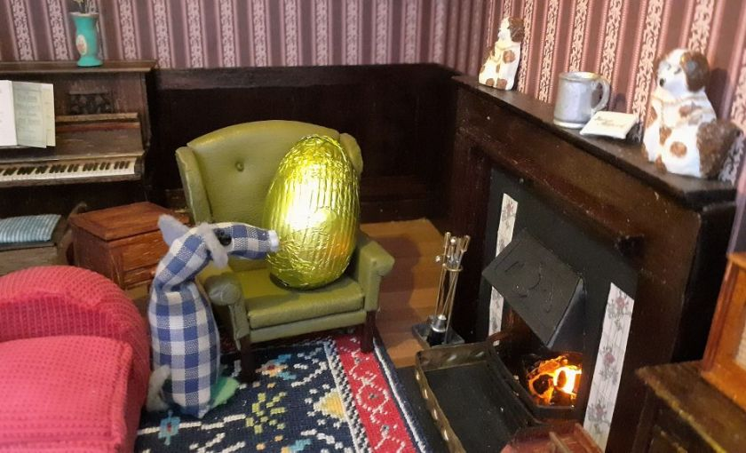 Microvaark looks at an egg sitting in an armchair in a miniature parlour.