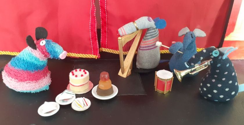 Ratvaark, with a cake, jelly and plates of sandwiches, looks at a group of vaarks playing instruments.