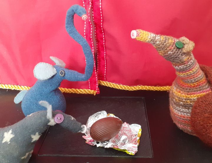 The egg is unwrapped to reveal chocolate, and Ernest waves his snozzle in joy