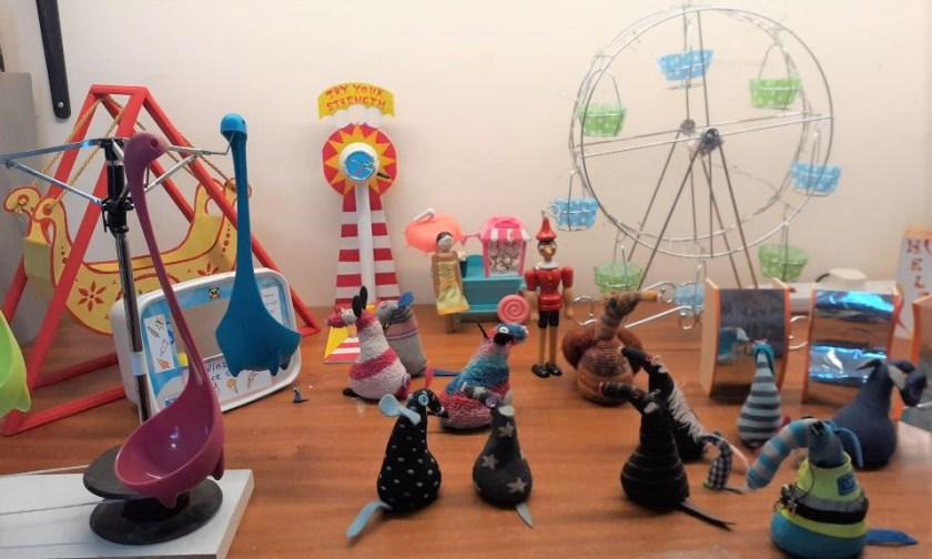 The vaarks gather on a table top with fairground attractions