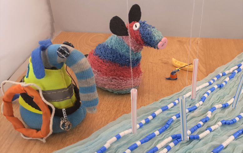 Arnold and Ratvaark and Nano stand beside a course of rough water with slalom poles hanging over it