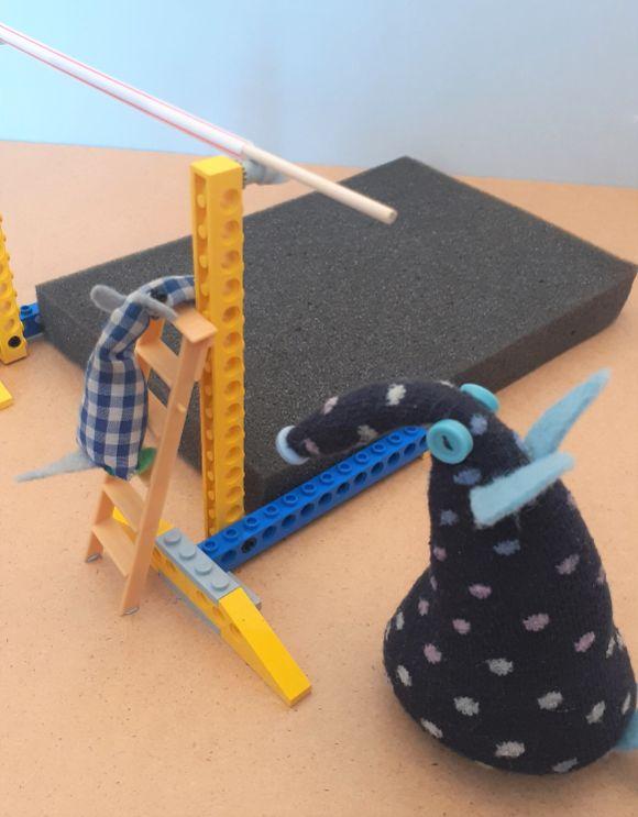 micro climbs a small step ladder to reach the bar