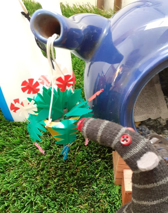Bernard looks at a hang basket of flowers, hanging from the teapot spout
