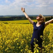 Woman in a field of wildflowers raising her hands to the sky in gratitude