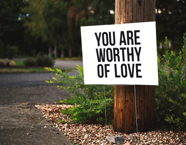 You are worthy of love sign on a tree