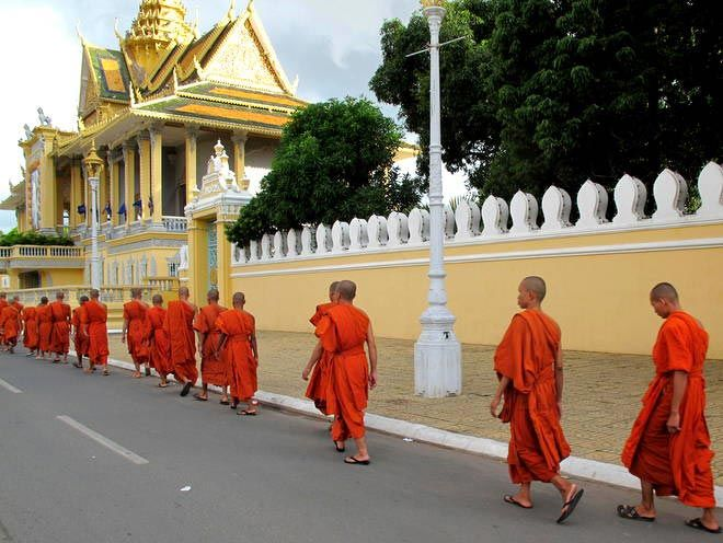 Saffron-clad monks streaming past Phnom Penh's Royal Palace.