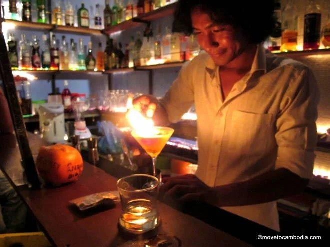 Hong Kry makes a drink with flair in a real tuk tuk at Siem Reap's Tuk Tuk Bar.