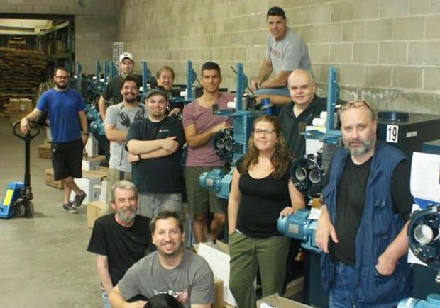 Boston Light & Sound's main projector and platter refurbish team, along with Cinemeccanica Victoria 8 projectors acquired for the project. (L-R, front to back) Rob Cejka, Michael Schaffer, Rick Campbell, Jess Jones, Larry Shaw, Adam Teti, Vincent Pagliaro, Al Lizotte, Geoff Hook, Jon Sharpe, Nick Rabchenuk, and Nathan Lizotte.