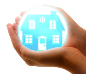 Two hands put together, holding a blue house, which seems to in in some kind of a ball that is illuminated. The picture gives a sense of a house which is being protected, and there is nothing better for that than moving insurance.