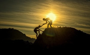 Two boys climbing a hill during sunset.