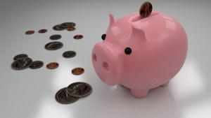 A pink piggy bank with coins around it.