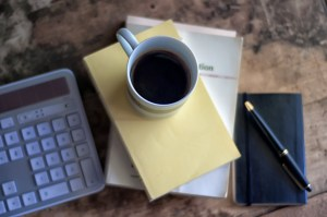 Cup of coffee, calculator, notebook, pen, laptop.