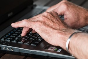 Senior typing on laptop, looking for movers Tenafly NJ.