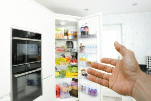 Hand pointing to open fridge, filled with food and beverages.