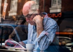 Older gentleman reading the paper in a coffee shop.