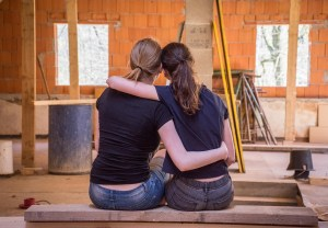 Two girls hugging after committing one of the mistakes first-time home buyers make.