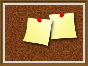 A cork board with two post it notes.