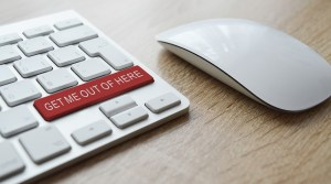 A red 'get me out of here' button on a white keyboard.
