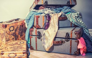 Jam-packed suitcases stacked on top of each other.
