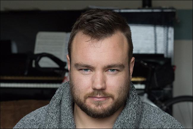 Portrait d'un homme photographié avec une ouverture de f / 5,6, résultant en un arrière-plan clair.