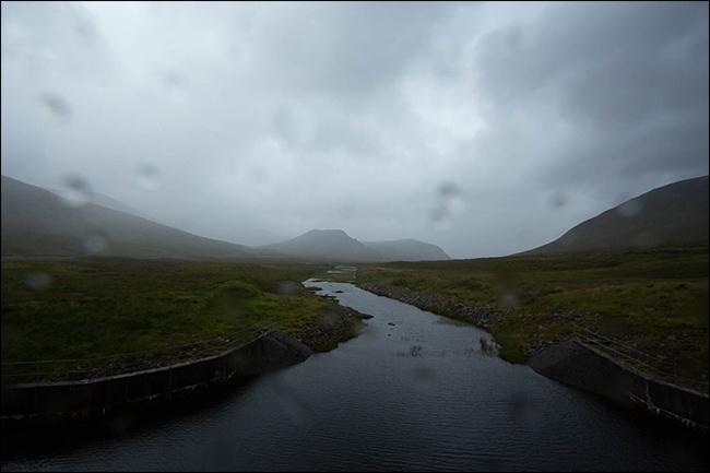 Une photo pluvieuse d'une montagne et d'un ruisseau avec des gouttelettes d'eau sur l'objectif.