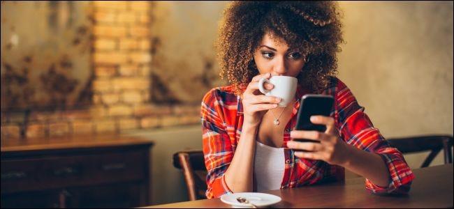 Una mujer sentada en una mesa mirando un teléfono inteligente y tomando café.