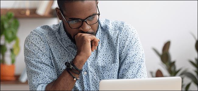 Un hombre está mirando su computadora y haciendo todo lo posible para ser honesto.