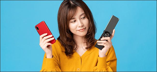 Una mujer sostiene un teléfono plegable y un iPhone.  Ella mira hacia el teléfono plegable, a un tiempo que pasó hace mucho tiempo ...