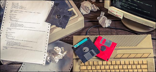 Un escritorio lleno de disquetes, equipos informáticos viejos y papel arrugado.