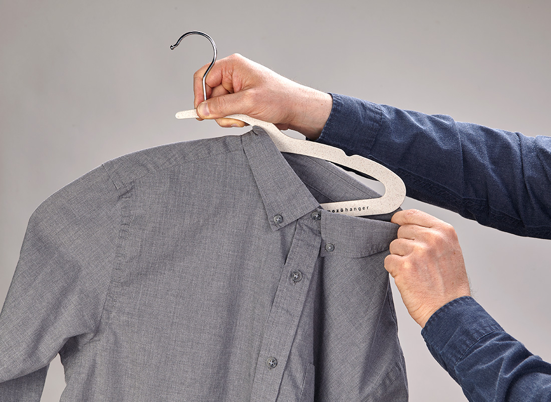 Buttoned dress shirt being removed from the wheat straw Mozu Hanger with top buttons buttoned